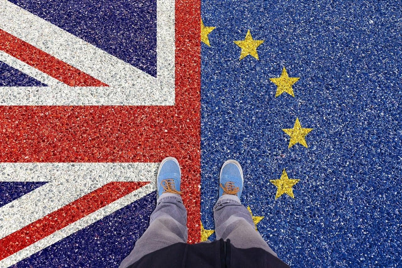 una persona pone un pie en la bandera de Reino Unido y otro en el de la bandera de la Unión Europea