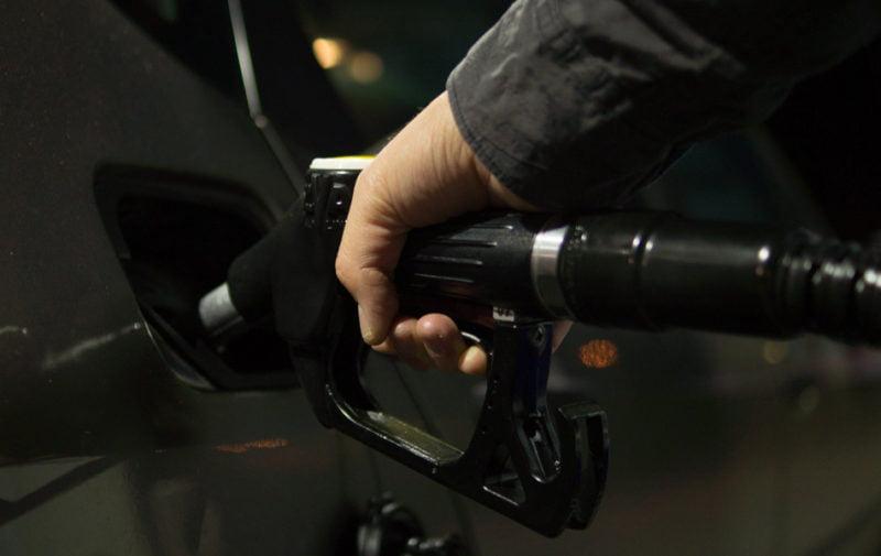 persona con la manguera de gasolina