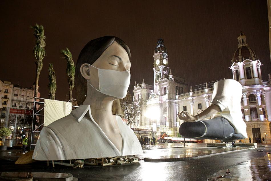 El monumento de fallas de el Ayuntamiento de València, sin concluir por la crisis del coronavirus, con una mascarilla puesta
