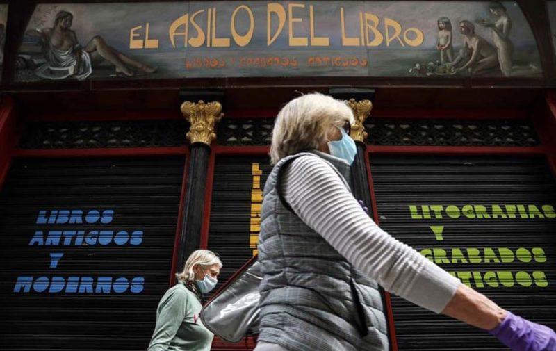 Dos mujeres pasan ante una librería cerrada en Valencia