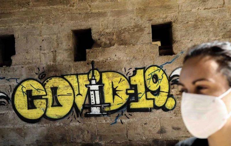 Una persona con mascarilla pasa ante un grafiti en Valencia