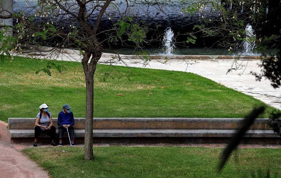 Personas mayores sentadas cerca del cauce del río Turia