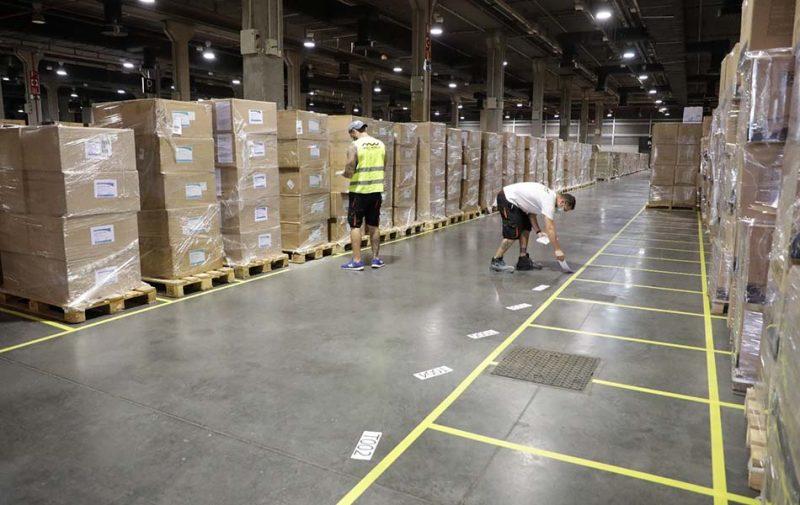 Dos operarios preparan espacio para ampliar capacidad de almacenamiento en Feria Valencia.