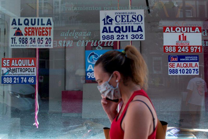 Una mujer con mascarilla pasa por delante de varios anuncios de viviendas en alquiler.