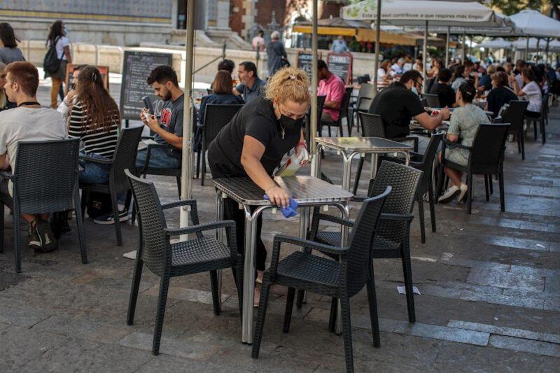 Una camarera desinfecta una mesa de una terraza en el centro de Valencia