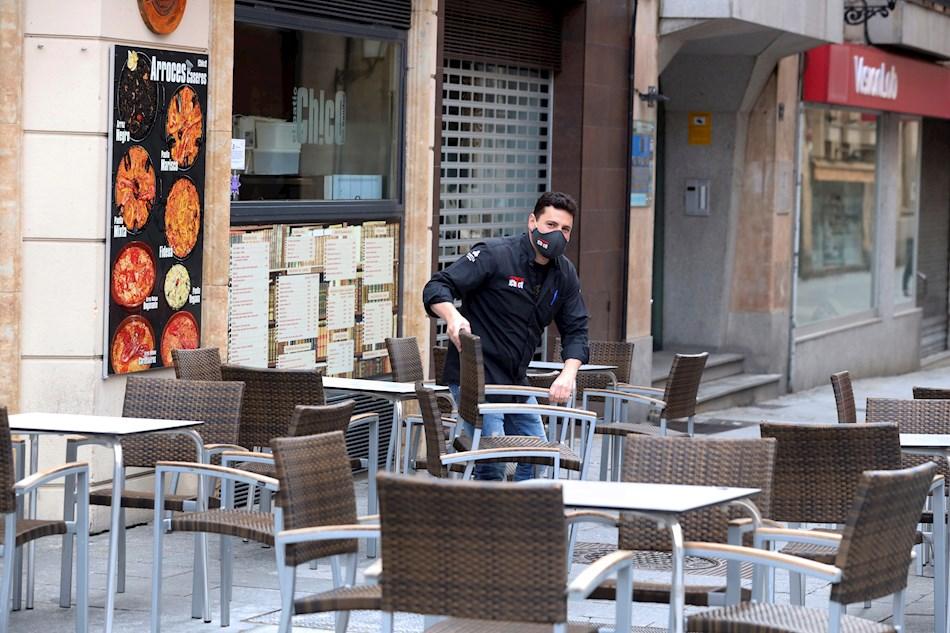 Un camarero coloca las sillas en un bar