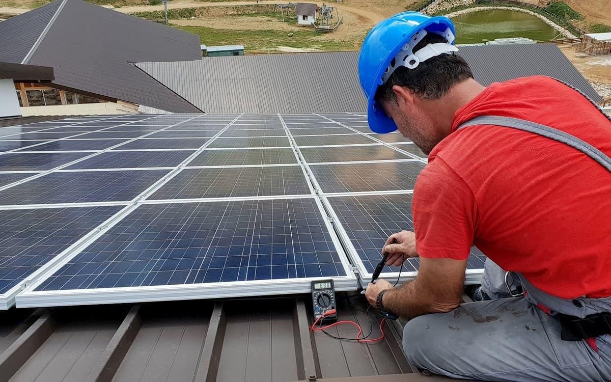 Un trabajador instala un tejado solar.