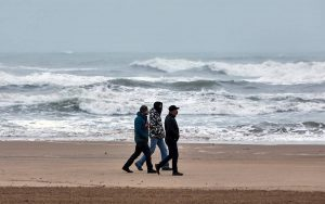 Varios hombres pasean por la playa de Gandia