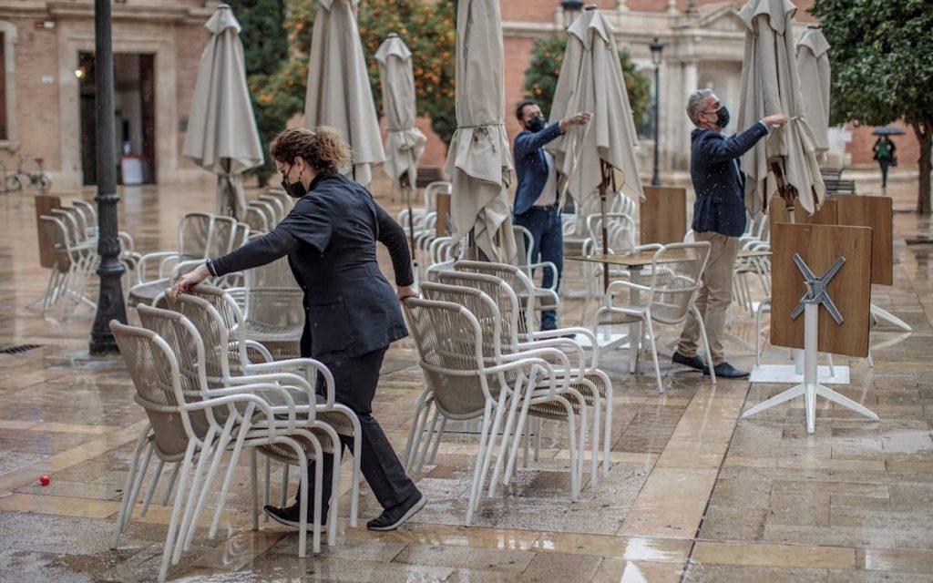 Camareros retiran la terraza de un bar. Pandemia.
