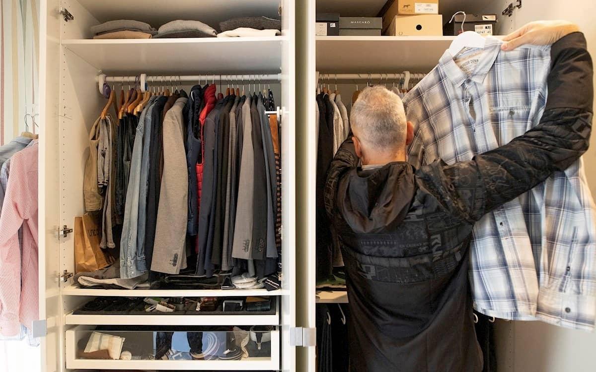 Un hombre ordena el armario de su casa