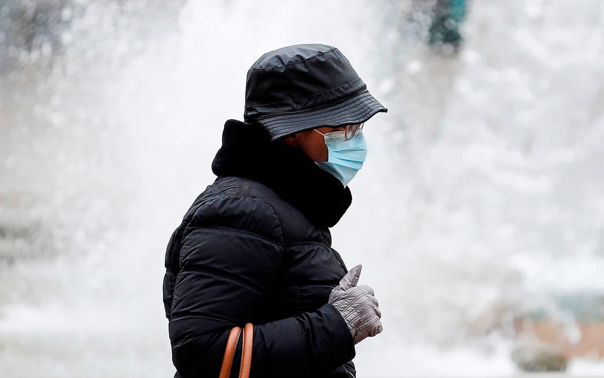 Una mujer se protege del frío hoy en la capital valenciana
