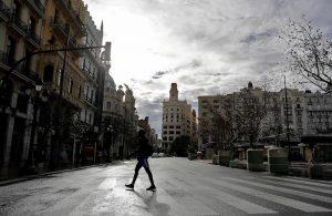 Un joven cruza una inusualmente tranquila plaza del Ayuntamiento de Valencia.