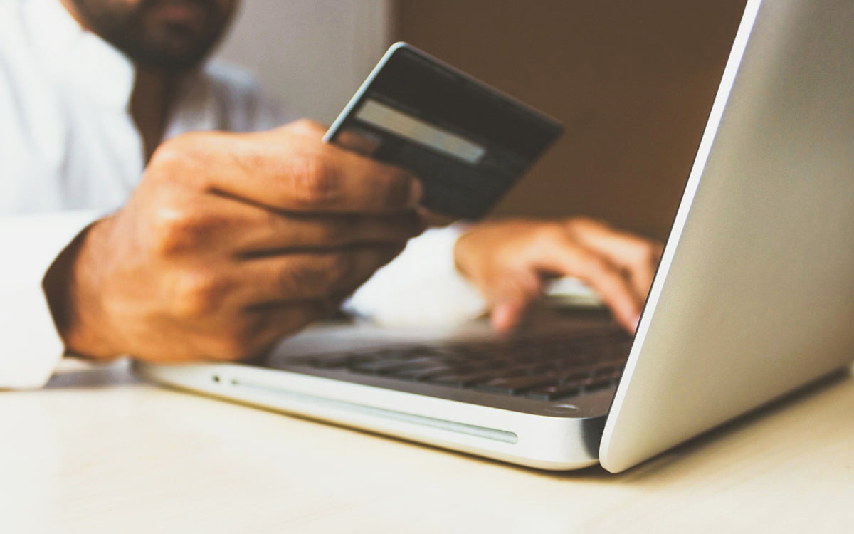 Una persona sostiene una tarjeta de crédito para realizar una compra a través de Internet.